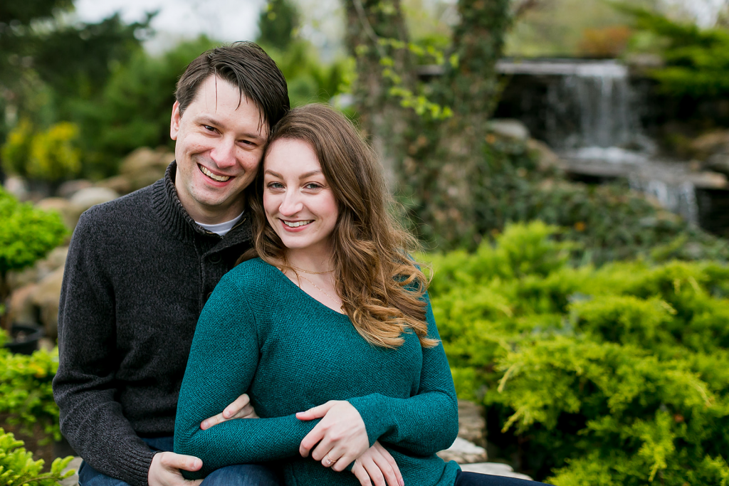 outdoors, smiling man in a black sweater, arms around a smiling woman in a teal sweater