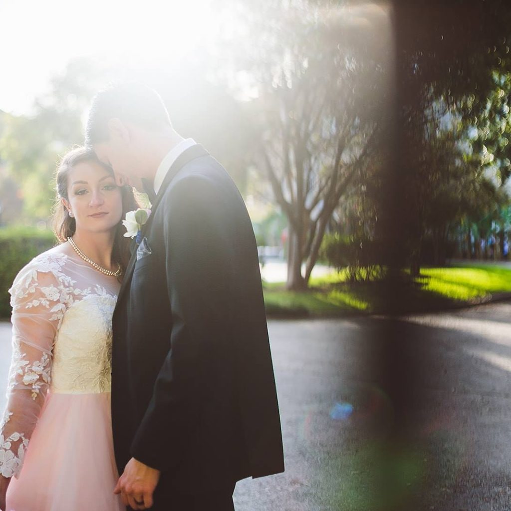a bride in a lace top and poufy pink skirt looks toward the camera while her husband, wearing a black tuxedo, presses his face to her temple