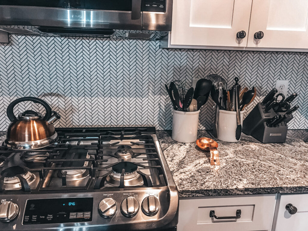 A close up of the black stainless steel range, white herringbone tile backsplash with dark grey grout, copper kettle, copper spoon rest, white utensil holders with various kitchen utensils, and knife block